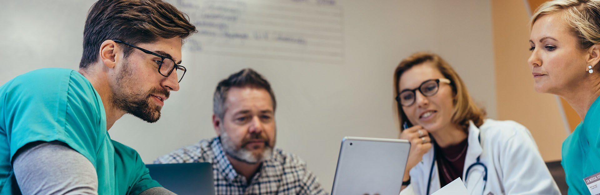 Eine Frau und zwei Männer schauen in den Bildschirm