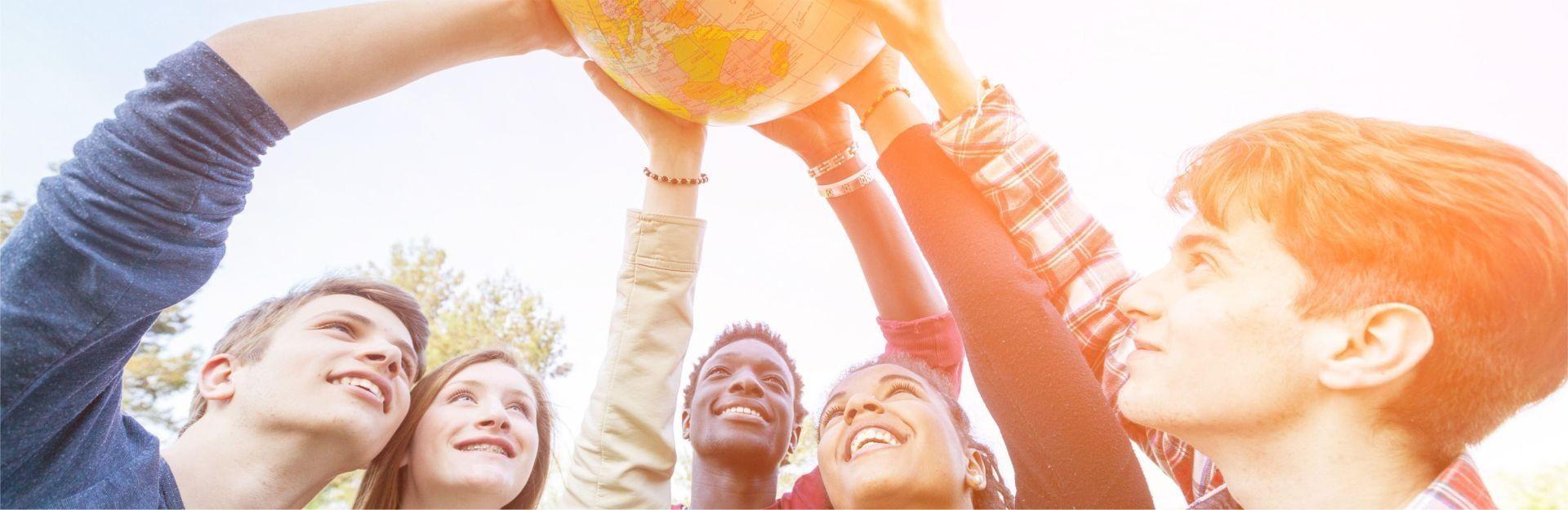eine Gruppe von Studierenden hält Globus in die Höhe