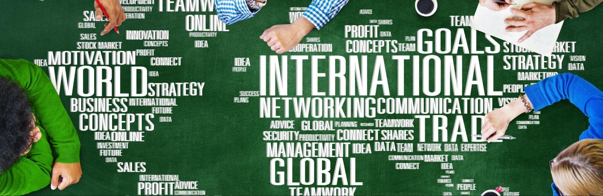 Menschen sitzen um einen Tisch mit internationalen Schlagwörtern