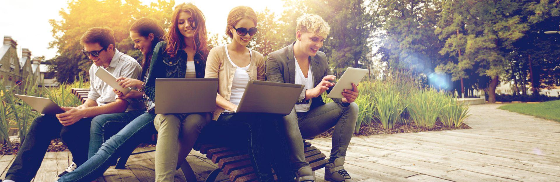 Jugendliche sittzen mit Laptops in der Sonne und lernen